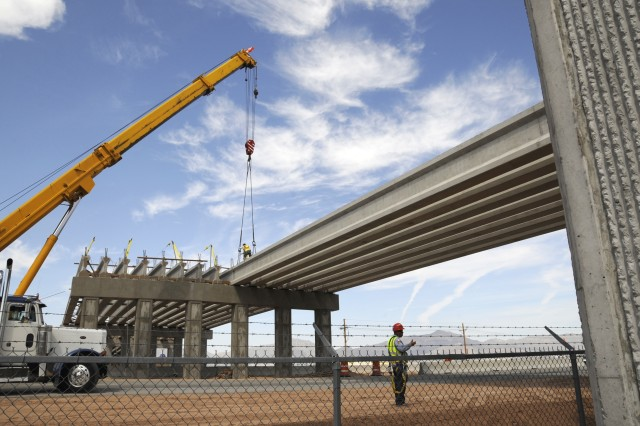 A worker, background, ensures placement of one of 15 beams in a span Saturday that will help make up the tactical bridge designed to cross Loop 375, join East Fort Bliss with the unfinished and eastern-most part of post.