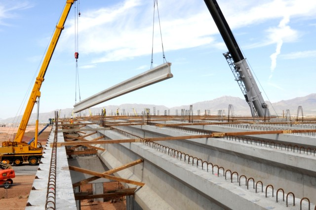 Two cranes lift a 100,000-pound bridge beam into place August 1 over Loop 375, which runs between the contained East Fort Bliss and the under-construction eastern-most part of Fort Bliss, Texas.