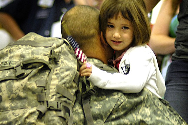 An unidentified Soldier hugs his daughter at the Dallas/Fort Worth International Airport in Texas after returning from Iraq. Soldiers such as the one pictured can now transfer Post 9/11 GI bill benefits to eligible dependents provided they meet eligibility requirements.