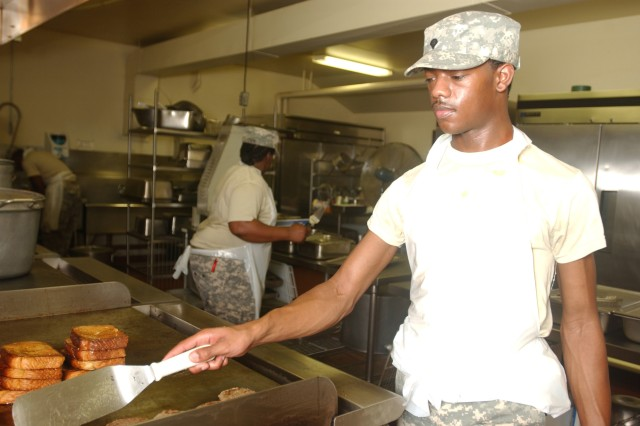 """Spc. Christopher Whigham, food service specialist, 377th Quartermaster Company, Tifton, Ga., prepares breakfast in the kitchen of the 352nd Combat Service Support Battalion dining facility.  Whigham and his fellow 352nd CSSB Soldiers are here in support of Golden Cargo 2009.  """""""