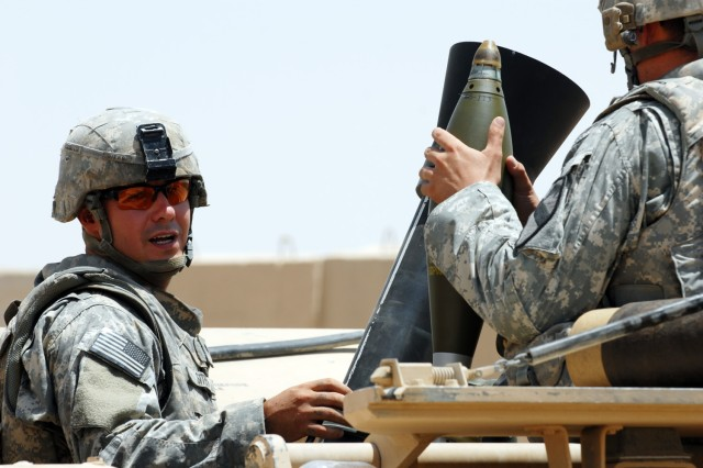 "BAGHDAD - Spc. Randy Sites (left), from Rising Sun, Md., communicates with Spc. Gordon Brooks from Tucson, Ariz., as they prepare to fire their first mortar since arriving in Iraq six months ago at Joint Security Station Istaqlaal, here. Both Soldiers are mortar men assigned to C Troop, 1st Squadron, 7th Cavalry Regiment, 1st Brigade Combat Team, 1st Cavalry Division. ""It definitely felt good to fire,"" said Sites after firing high-explosive mortar rounds July 31. ""It got the cobwebs out."""