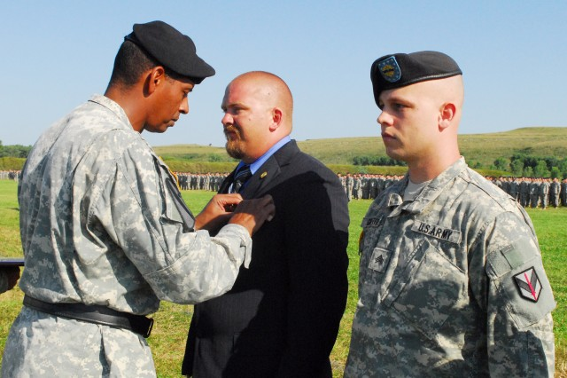 """Maj. Gen. Vincent Brooks, commanding general of the 1st Infantry Division and Fort Riley, awards David Sterling, II, with the Silver Star during the Victory Week pass in review ceremony July 31.  Sgt. Damien Griffith and Spc. Jessica Ross (not pictured), both of 1st Sustainment Brigade, received Purple Hearts for wounds sustained while deployed to Iraq."""""""