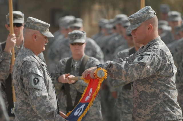BAGHDAD - Command Sgt. Maj. John Morgan III (left), senior enlisted leader of the 56th Infantry Brigade Combat Team, 36th Infantry Division, Multi-National Division - Baghdad, along with Col. Lee Henry, commander, 56th IBCT, roll up the brigade's colors in preparation for casing and transport back to Texas as the 56th becomes 'mission complete' after 243 days during an Aug. 1 transfer of authority ceremony held with the 41st IBCT of the Oregon National Guard at Camp Victory.
