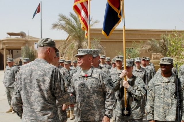 BAGHDAD – Maj. Gen. Daniel Bolger (left), commanding general, 1st Cavalry Division and Multi-National Division – Baghdad, presents Col. Lee Henry, commander, 56th Infantry Brigade Combat Team, 36th Inf. Div., with the Bronze Star Medal for Meritorious Service while serving as the commander of the Base Defense Operations Center at Victory Base Complex during a surprise award ceremony prior to the 56th IBCT's transfer of authority ceremony held with the 41st IBCT of the Oregon National Guard at Camp Victory on Aug. 1. Henry, of Austin, Texas, was kept unaware of the award presentation until the last moment.