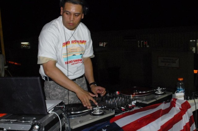 "BAGHDAD - ""DJ Jimmy"", otherwise known as Pfc. Jaime Paizlones, 29, of New Orleans, La., with the 225th Engineer Brigade, scratches Kanye West's 'Flashing Lights' on the turntable to entertain the crowd that attended a talent show on the Liberty PX stage on July 31. Paizlones, a medic, purchased his music equipment to give something back to Soldiers on the weekends at Camp Liberty. ""I want them to relax and enjoy themselves after a stressful week,"" said Paizlones."