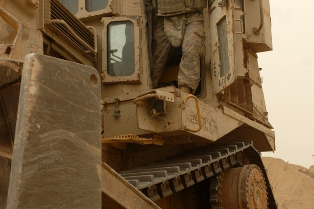 "BAGHDAD - Spc. Franklin Cardenas, Army Reserve heavy equipment operator assigned to the 277th Engineer Company, 46th Eng. Bn., 225th Eng. Bde., exits from a D-9 bulldozer after clearing an area of rocks in northeast Baghdad, July 30. The D-9 bulldozer is the largest piece of engineering equipment the military has. ""I like being able to come out and move dirt,"" said Cardenas, a native of Luling, Texas. ""It's rewarding and there's a feeling of self-satisfaction."""