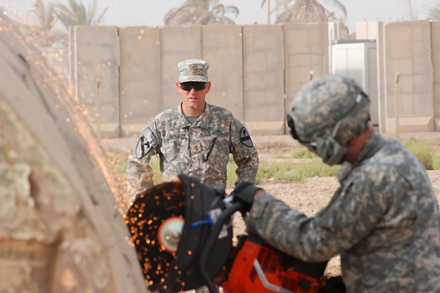 CAMP TAJI, Iraq-Maj. Marcus Gengler (center), of Ontario, Calif., commander, Company B, 615th Aviation Support Battalion, 1st Air Cavalry Brigade, 1st Cavalry Division, Multi-National Division - Baghdad, observes one of his Soldiers operating a chop saw, July 30, on the outskirts of Camp Taji, Iraq. This training event focuses on teaching Soldiers from the Downed Aircraft Recovery Team how to properly handle the powerful saw in case of a downed aircraft situation.