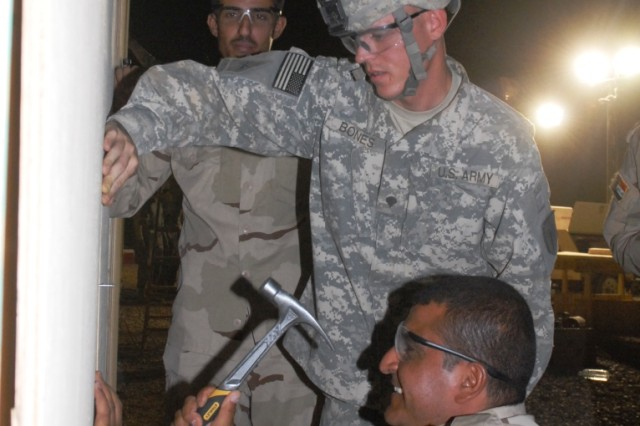 BAGHDAD - Spc. Eric Bones, of Pipestone, Minn., watches as Sgt. Ali Faris Alowarn hammers nails into the side of B-Huts in al-Rasheed in the Rusafa district of central Baghdad, July 30. The B Company, 46th Engineer Combat Battalion (Heavy), 225th Engineer Brigade partnered with the 9th Iraqi Army Engineer Regiment to build five housing units for Soldiers.