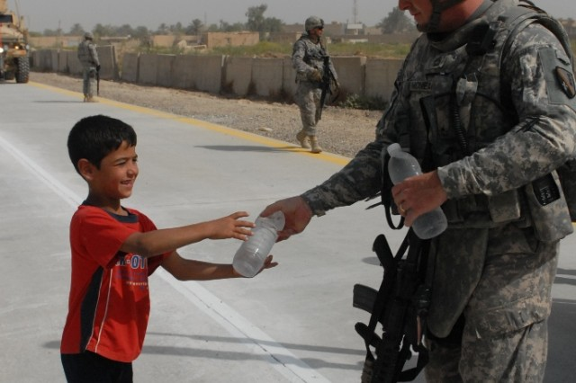 BAGHDAD - Sgt. 1st Class Chad McNeal, 225th Command Security Team noncommissioned officer-in-charge, Marksville, La., gives a bottle of water to an Iraqi child who lives along the newly paved Maya Road just outside of Victory Base Complex. The 225 CST provided security during the Aug. 1 final road inspection.