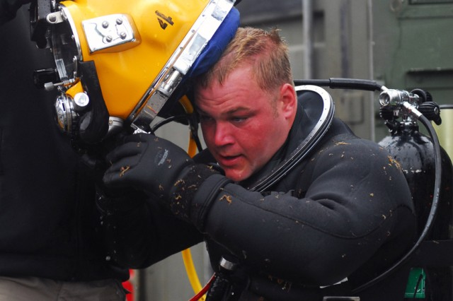 Spc. John Hoover, a 2nd class diver with the 7th Diving Team, removes the diving helmet of Pfc. Britton Hall, also a 2nd class diver on the 7th Diving Team, after his dive. The team is in Ketchikan, Alaska, repairing a floating breakwater in Bar Point Harbor.
