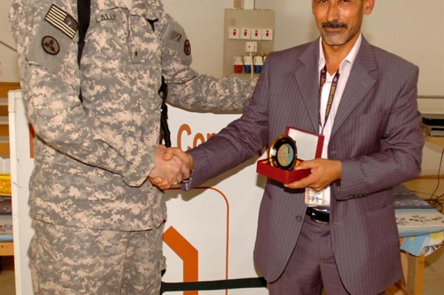 Brig. Gen. Michael J. Lally, 3d Sustainment Command (Expeditionary) commanding general, accepts an award from Hashim Abd Al-Amir Mahdi, owner of the Miran Village Company, as a symbol of appreciation for his leadership involving the container repair yard during a ceremony here, July 27.  The ceremony celebrated the certification of the Miran Village Co.'s workers by Iraq's Ministry of Labor and Social Affairs. (U.S. Army photo by Spc. Michael Behlin)