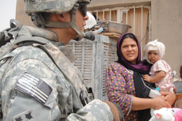 Rawaa Saod Najiem's mother talks to a Soldier from Battery B, 3rd Battalion, 82nd Field Artillery Regiment, 2nd Brigade Combat Team, 1st Cavalry Division, July 22 about the surgery her daughter underwent two days prior. Battery B Soldiers were the first outside of her village to discover Rawaa's injuries and helped find aid for her through the local Iraqi Police.