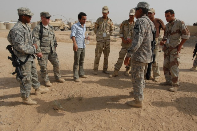 Iraqi Army soldiers and instructors from 1st Battalion, 8th Cavalry Regiment, 2nd Brigade Combat Team, 1st Cavalry Division, inspect a mound of dirt that contains a hoax Improvised Explosive Device on Forward Operating Base McHenry, Iraq, July 22. These IA soldiers are going through a nine-day course to instruct them on the basics of route clearance. These skills learned during the training will help them detect the location and types of IEDs.