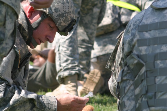 A military transition team member with Class 78 assists an unresponsive person during simulated Combat Life Saver training July 31 at Camp Funston, Fort Riley. Class 78 is the last Military Transition Team to train at Fort Riley before the mission moves to Fort Polk, La.