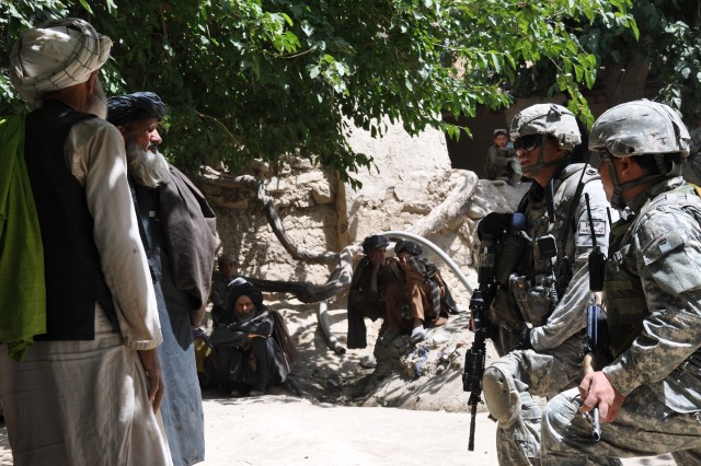 Capt. Jason V. Basilides, a 1st Battalion, 4th Infantry Regiment, platoon leader from Virginia Beach, Va., speaks to local leaders through interpreter Najeeb Ghafoori during a foot patrol, July 27, in Deh Chopan district, Zabul province.