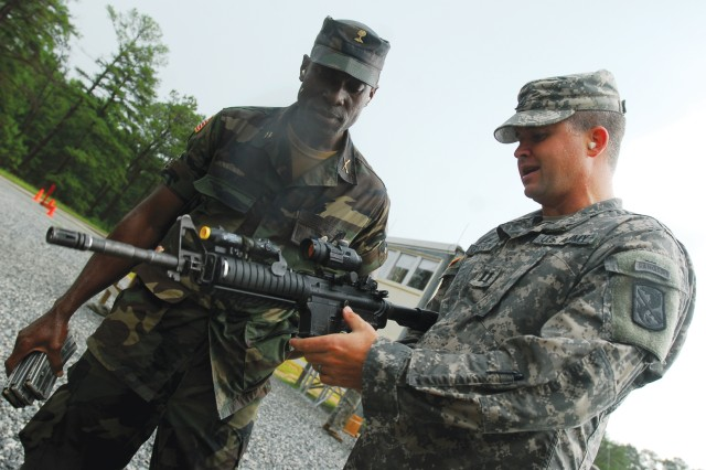Armed Forces of Liberia Maj. Andrew Wleh and Capt. Ryan Gamston, commander of B Company, 2nd Battalion, 19th Infantry Regiment, discuss marksmanship training during Wleh's visit.