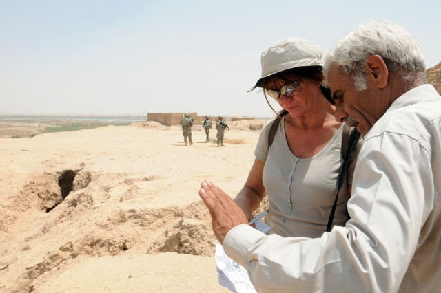 Diane Siebrandt, an archeologist and cultural heritage officer at the United States Embassy Baghdad, speaks with Dr. Mohammed Ajaj Jorjis, the former Ashur site director, who explains a map of the ancient Assyrian capital of Ashur. The visit gave Siebrandt, the ability to document the condition of the ruins and promote the preservation of the historical city, July 26.