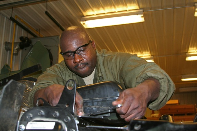 A native of Mableton, Ga., Staff Sgt. Walter Chambers, a mechanic with the 1015th Maintenance Company, Fort Gillem, Ga., replaces a fan clutch on a M915 tractor trailer during Golden Cargo 2009 (July 20) exercise at Crane Army Ammunition Activity. The exercise is designed to offer real-world training to Army Reserve ordinance and transportation companies while completing an essential mission of delivering ammunition to the war fighters.