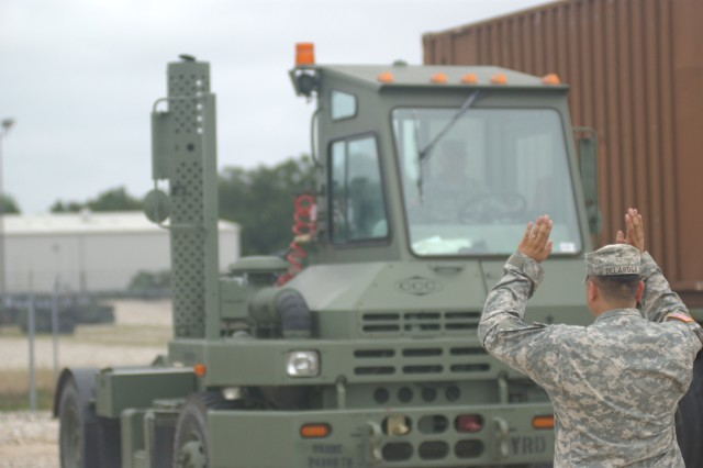 Staff Sgt. Robert Delarosa, the detachment noncommissioned officer in charge for the 189th Trailer Transfer Point Detachment, ground guides an M878A2 yard tractor driven by Sgt. Mark Swinarski at Fort Leonard Wood, Mo., at an equipment consolidation site that is being used during Golden Cargo 2009. The 189th TTPD is an Army Reserve unit headquartered in Council Bluffs, Iowa.