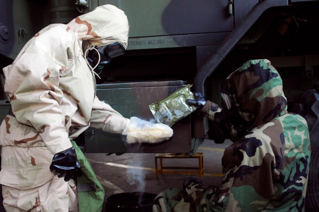 Sgt. Chasity N. Yeager, Team Leader, Bravo Company, 412th ASB, and Sgt. Robert E. Blackwelder, Chemical, Biological, Radiological, Nuclear NCO, 4/2 Stryker Combat Regiment, decontaminate a vehicle using the M100 decon kit.  The M100 reactive sorbent powder is highly effective and more efficient in decontaminating military equipment.