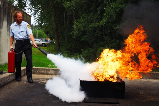 Otto Sperber, a fire inspector at the Vilseck Fire Station, demonstrates how to douse a fire using the CO2 training extinguisher before 25 Soldiers attempt to do the same. Sperber taught the Soldiers the differences between U.S. and German regulations for hazardous material transportation safety so the Army can keep Europe's roads safe.