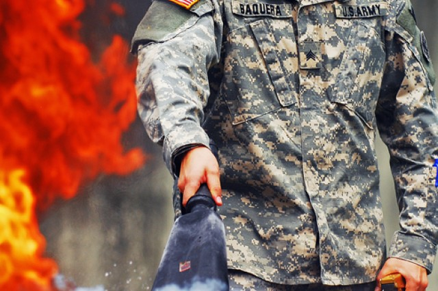 Sgt. Adrian Baquera suffocates a six-foot tall fire at the Vilseck Fire Station during a hazardous materials course offered by the Joint Multinational Training Command's Combined Arms Training Center in Vilseck, Germany, July 23.