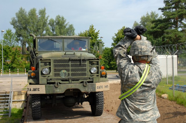 1st Lt. William Huerth, 44th Expeditionary Signal Battalion, guides the driver of a M939 5-ton truck during a loading exercise at the Vilseck , Germany, July 22. The exercise was part of the Unit Movement Officer (UMO) course evaluation in which students demonstrate how to properly load military equipment for movement by rail.