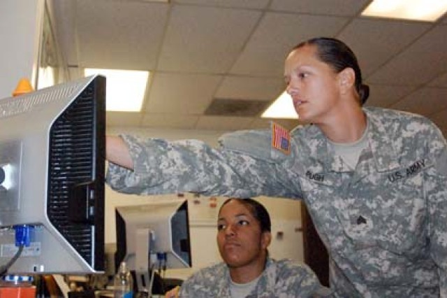 Sgt. Melissa Pugh, Adjutant Corps General Soldier of the Year, works through an administrative issue with a junior enlisted Soldier.
