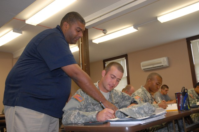 James Keels, an instructor at the Army Preparatory School at Fort Jackson, S.C., discusses a math problem with Soldier and student Pfc. Daniel McAfee of Tampa, Fla.