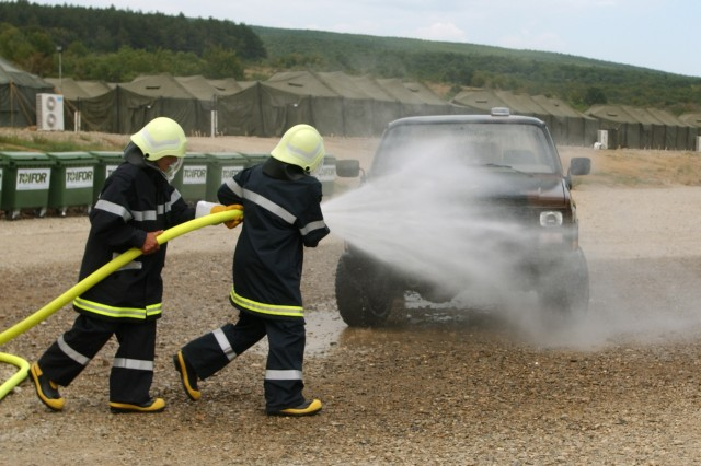 NOVO SELO TRAINING AREA, Bulgaria - Dinko Yanchev, left, and Penyo Zhekov hose down a vehicle during a simulated fire drill here Aug. 5. Firefighting training conducted here is part of Joint Task Force-East to help participants improve their lifesaving capabilities.