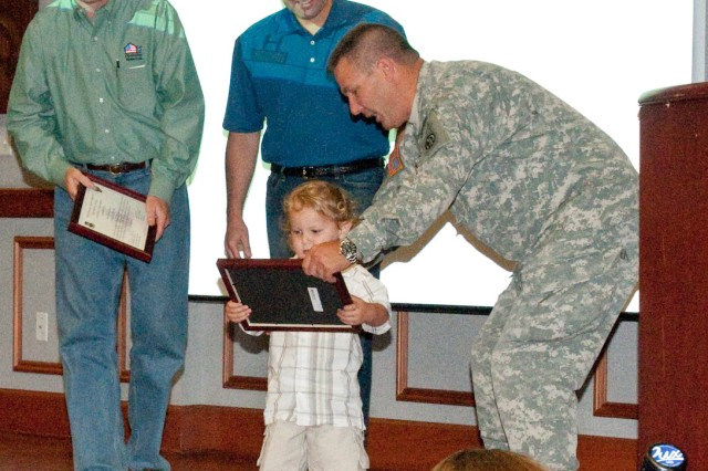 Col. Mark Stammer, commander of 1st Brigade Combat Team, 82nd Airborne Division, enlists a young spectator to help present Dan Shannon of Operation Homelink and Troy West of Dell Computer with plaques of appreciation for gifting the families of 75 Soldiers with computers to keep in touch with their soon-to-deploy Soldiers.