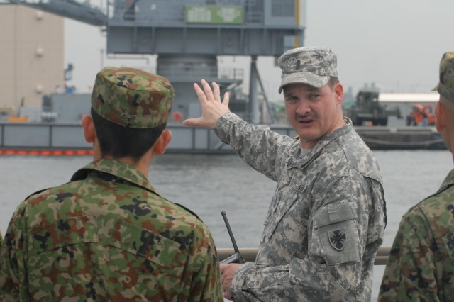 Chief Warrant Officer Walter Spurling, Exercise Pacific Reach operations officer, briefs a group of Japanese Ground Self Defense Force Soldiers on the capabilities of the Barge Derrick Crane, Aug. 12, at Yokohama North Dock, Tokyo, Japan.