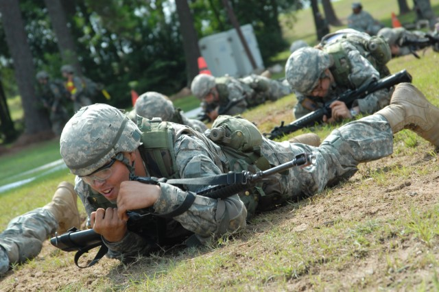 Soldiers with Company E, 1st Battalion, 61st Infantry Regiment high crawl during a combat physical readiness test in front of the Welcome Center last week. Soldiers were divided into teams by squad and completed a timed course consisting of a 50-meter high crawl, 150-meter sprint, pull-ups, 100-meter supply carry and carrying a casualty for 100 meters.