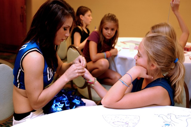 Orlando Magic Dancer Erin Gomerall helps Samantha Smith, 11, with a friendship bracelet during a recent visit to the 81st Regional Support Command's Yellow Ribbon Reintegration Program held in Orlando Aug. 7-9. More than 75 sons and daughters of Soldiers who recently returned from combat tours in Iraq and Afghanistan were signed up for the child care program designed to entertain the Army Reserve youth as their parents were busy learning how to reintegrate back into their families and communities after a deployment overseas.