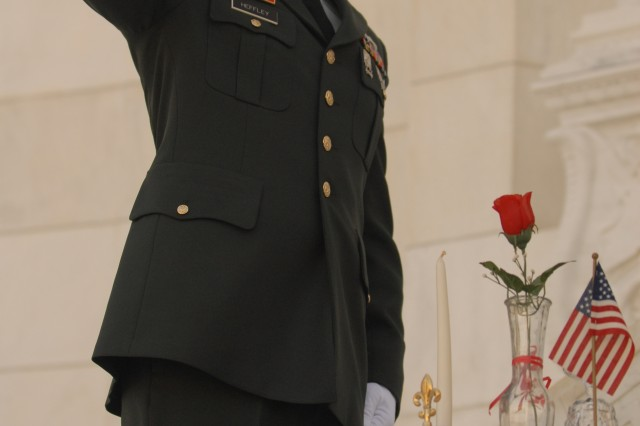 Staff Sergeant Michael Heffley, a military policeman with the 212th Military Police Detachment, Fort Belvoir, Va., salutes the fallen Soldiers of the 3rd Infantry Division in a ceremony at Arlington Memorial Amphitheater in Arlington National Cemetery. The POW/MIA table in front of him holds items of significance to the Family Members and the grateful nation they fought for.""