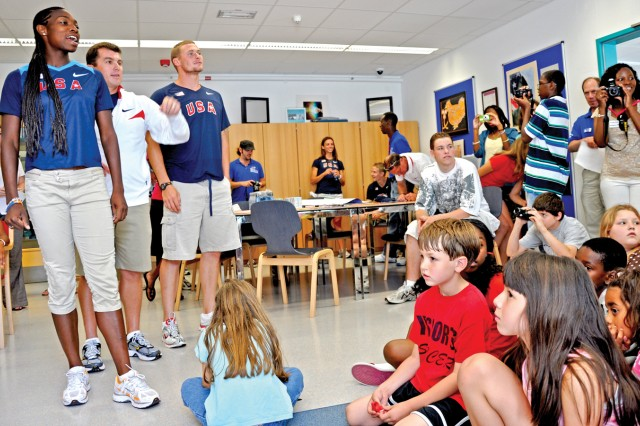 Members of the U.S. National Track and Field Team Lela V. Nelson (left), Olympian Paul Terek (right) and men's head coach Mario Sategna talk to Wiesbaden youths before competing at the Thorpe Cup in Marburg Aug. 8-9.