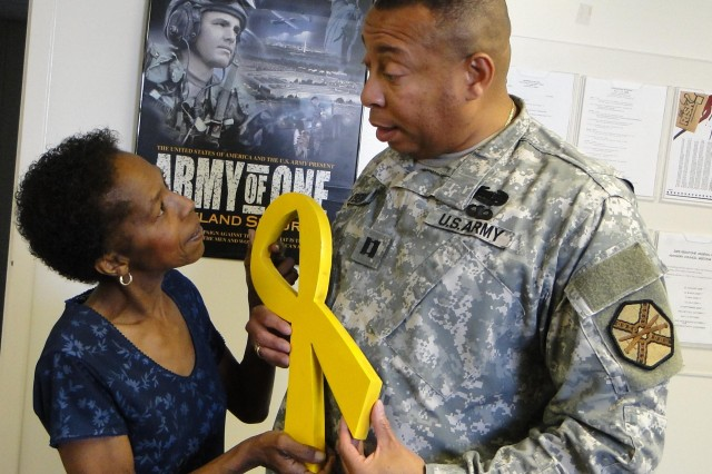 Ruby Turner, director of the Employee Assistance Program, talks to Capt. Rob Dewberry, commander of Garrison's Headquarters & Headquarters Company, about the yellow ribbon's significance during Suicide Prevention Month. Yellow ribbons will be given to Arsenal employees in hopes of raising awareness of suicide prevention.