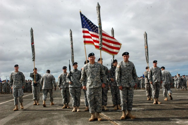 """Col. Mike Lundy (left), commander, 25th Combat Aviation Brigade (CAB), and Command Sgt. Maj. Jesus Ruiz, brigade command sergeant major, stand before the brigade's cased colors during the CAB's deployment ceremony at Wheeler Army Airfield, Aug. 10. The casing of the unit's colors signifies the start of their 12-month deployment to Iraq, where the 25th CAB will assume responsibility for aviation operations in northern Iraq as part of Task Force """"Marne."""""""