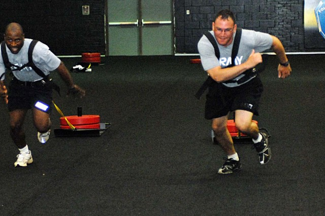 SGT Demiso Aarington and SSG Fernando Avila of 362nd Engineer Company (Multi-Role Bridge), race with weight sleds Tuesday in the athletic performance enhancement room.