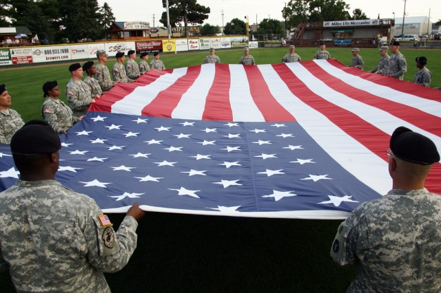 Soldiers from the 33rd Brigade Combat Team and the 81st Brigade Combat Team hold a large U.S. Flag during opening ceremonies at the Military All-Stars versus La Crosse All-Stars baseball game.