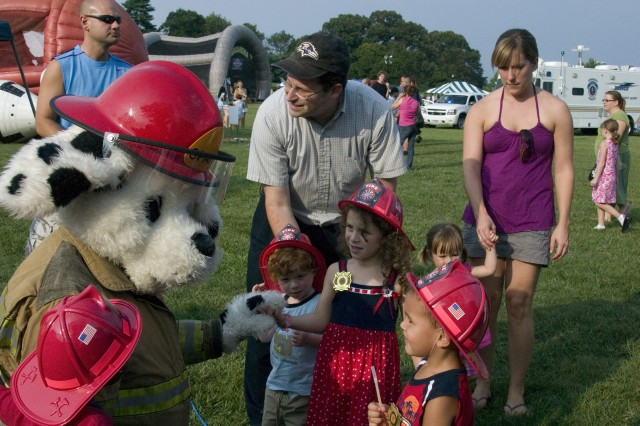 Ruthy Feinstein, 5, of Baltimore, meets the mascot of fire safety, Sparky the Fire Dog, at the start of National Night Out held Tuesday evening on McGlachlin Parade Field. More than 4,000 people attended the annual crime-prevention event that featured live music, K-9 unit demonstrations, inflatable play zones, paint ball, free food, Bubbles the clown and the landing of a police helicopter.