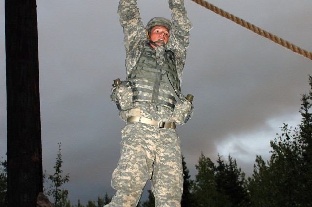 Pfc. Joshua Furbeck, a gunner with the 472nd Military Police Company from Fort Wainwright, Alaska, lowers himself from the rope climb during the obstacle course portion of the Warrior Police Challenge tryouts Aug. 6, at Fort Richardson, Alaska.