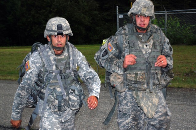 Staff Sgt. Paul Ramos, a squad leader with 472nd Military Police Company from Fort Wainwright, Alaska, and Spc. James Teare Jr., a team leader with 164th Military Police Company from Fort Richardson, Alaska, ruck march to the obstacle course at Fort Richardson during Warrior Police Challenge tryouts, Aug. 6.
