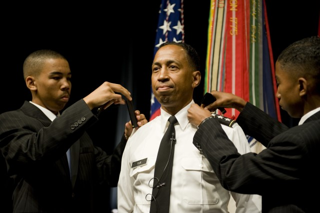 Lt. Gen. Dennis Via's two sons, Brian and Bradley, apply their fathers new rank to his shoulder boards during the promotion ceremony in Arlington, VA., on Aug 14, 2009.