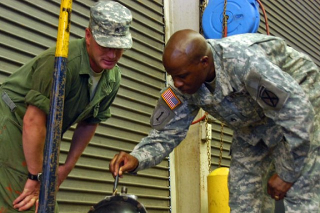 Staff Sgt. Louis Whaley (right), battalion motor sergeant for 2nd Battalion, 30th Infantry Regiment, points to a problem as he and Sgt. Dustin Rowland, Maintenance Support Team 2 squad leader, Company F, 94th Brigade Support Battalion, examine a differential in the 2nd Bn, 30th Inf Reg motor pool July 14.