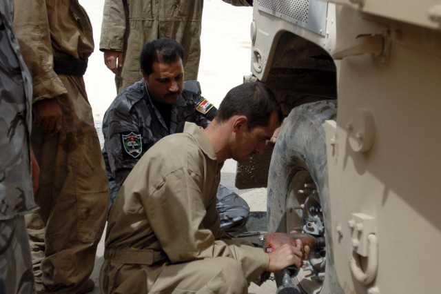 Sgt. Joseph Benson, a track mechanic with 215th Brigade Support Battalion, 3rd Heavy Brigade Combat Team, 1st Cavalry Division, observes an Iraqi policeman with the 4th Emergency Response Battalion, Ninewa Provincial Police, as he tightens humvee lug nuts during a training exercise Aug. 12, in Mosul, Iraq.