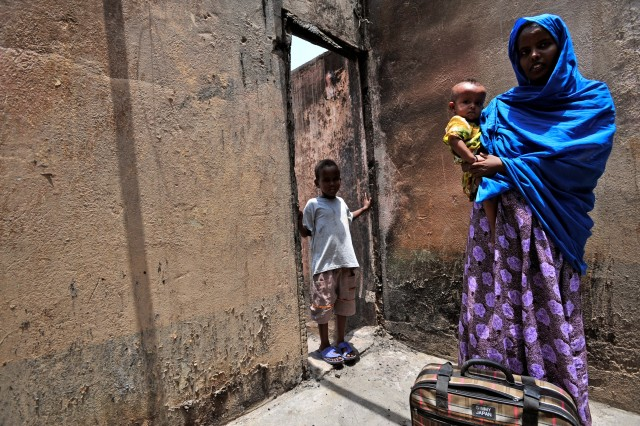 Zamzam Ahmed Dinbil stands holding her child in the burned remains of her home in Djibouti, Aug. 12, 2009. Her home was one of 21 homes destroyed in a fire two days earlier in a neighborhood in the Boulaos commune in Djibouti. Soldiers from the 478th Civil Affairs Battalion and sailors from Maritime Civil Affairs Team 104, assigned to Combined Joint Task Force - Horn of Africa, delivered supplies and donated material to the victims.