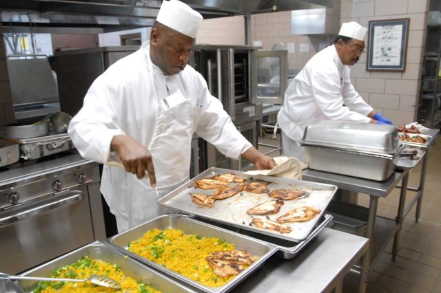 Alberto Cordew (left) and Jerome Farmer, both employees at the USASOC Dining Facility, prepare teriyaki catfish and barbeque chicken for the lunch meal. (Photo by Sgt. Tony Hawkins, USASOC PAO)