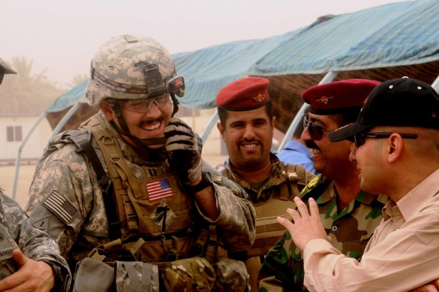Capt. Allen Trujillo, commander of Company D, 4th Battalion, 6th Infantry Regiment, meets with Iraqi police training academy instructors following the July 30 graduation ceremony of 875 police officers.
