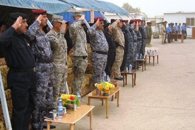 Leaders from 4th Battalion, 6th Infantry Regiment and Iraqi Police in Maysan render honors during the playing of Mawtini, the Iraqi national anthem, during a ceremony for 875 graduates of the Iraqi police basic recruit training graduating class July 30.